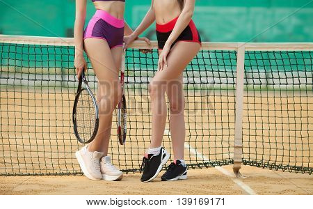 Two sexy slim fitness woman long legs in sports clothing holding tennis racket on clay court
