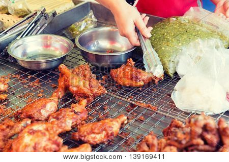 cooking, asian kitchen, sale and food concept - close up of cook hand with tongs grilling chicken