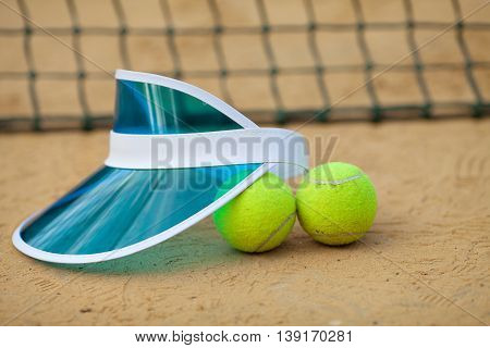 Clay tennis court with tennis ball, netting, cap.