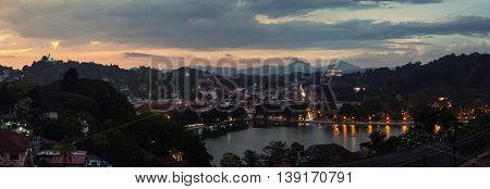 Lake in Kandy. Sunset over the former capital of Sri Lanka. Panoramic view at night with car light trails