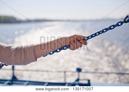 Girl clings to the chain on river background.