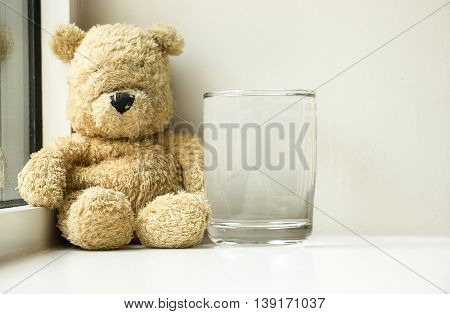 Bear is sitting down with a glass of water