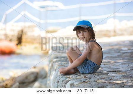 Cute Boy, Sitting On A Pier In Mediterranean Sea On French Riviera