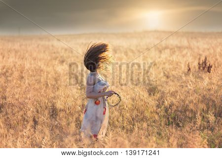 Summer portrait of a young woman, in the wheat field, at sunset