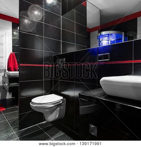 Spacious stylish and modern bathroom in black with red details white basin and toilet