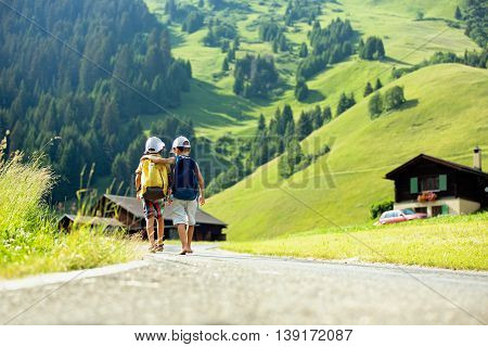 Two Little Children, Boy Brothers With Backpacks Travel On The Road To Scenic Mountains
