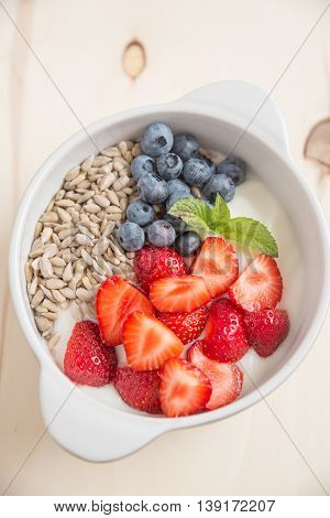 yoghurt with granola and fresh berries in a bowl