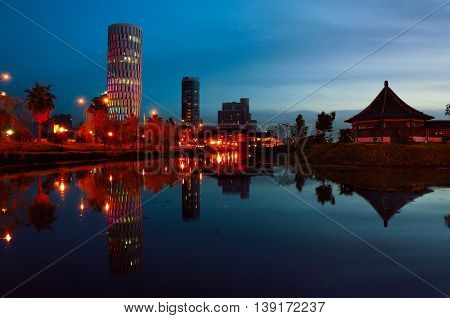 Palace of Justice in Batumi, Georgia at night with reflection at the pond. Dark blue sky and illuminated buildings