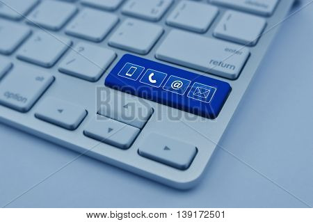 Telephone mobile phone at and email icon on modern computer keyboard button Customer support concept blue tone