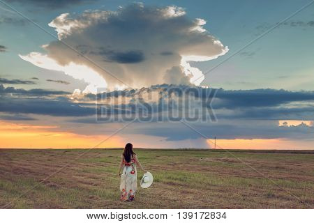 Portrait of a young woman in a wheat field at sunset