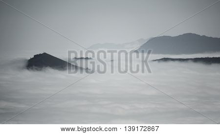 Detailed view of beautiful clouds and fog below mountain range, dark image in black and white