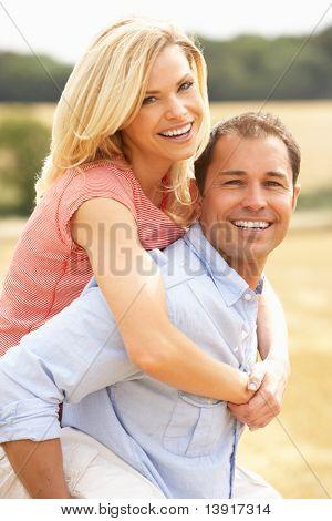 Couple Having Piggyback In Summer Harvested Field