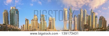 Panoramic view of Dubai Marina bay with yacht and cloudy sky, Dubai, UAE.