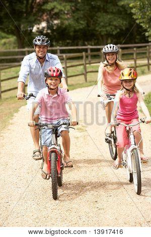 Familie Radfahren In Landschaft tragen Schutzhelme