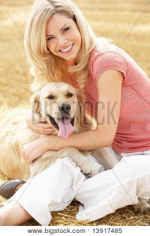 Woman Sitting With Dog On Straw Bales In Harvested Field