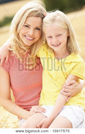 Mother And Daughter Sitting On Straw Bales In Harvested Field