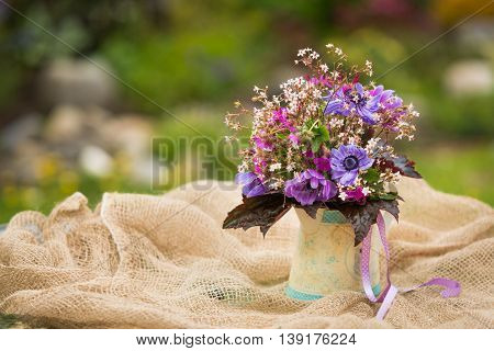 Garden style summer bouquet. Mix of lilac and purple anemone flowers, geranium flowers and heuchera or alumroot leaves. Bouquet on sackcloth background in decorative pot. Garden style wedding bouquet