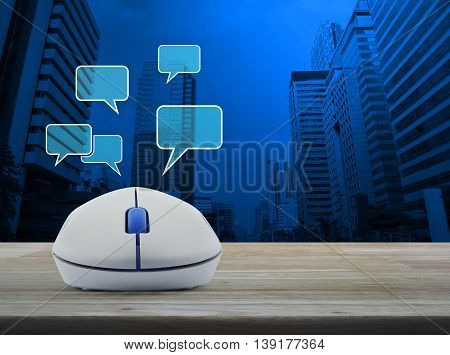 Wireless computer mouse with social chat sign and speech bubbles on wooden table in front of city tower background Social network concept