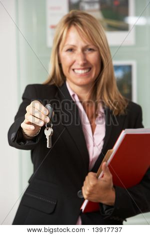 Portrait Of Female Estate Agent In Office Handing Over Keys