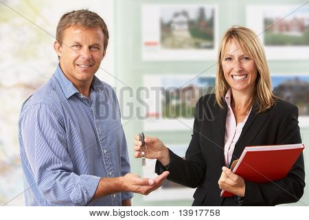 Female Estate Handing Over Keys Of New Home To Client