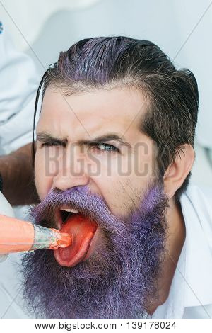 Young man with handsome serious face lilac beard eating orange cream with open mouth on white background closeup