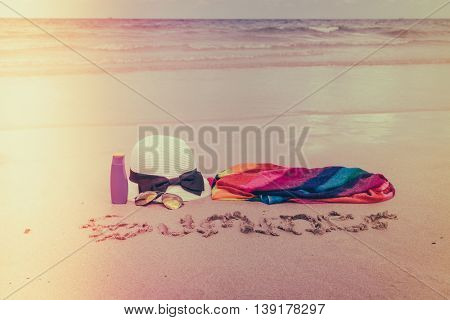 Sunglasses, sun cream and hat  on white  sand beach - Filtered image processed vintage effec