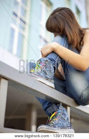 Sad lonely girl meditates sitting on the railing of the city (focus on trendy sneakers)