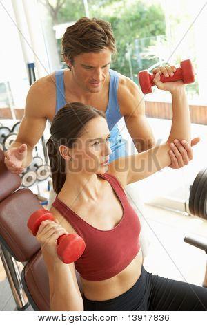 Joven trabajando con pesas en el gimnasio con Entrenador Personal