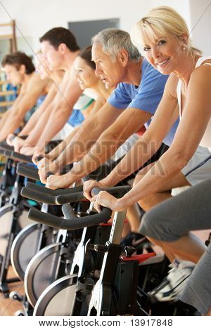 Senior Woman Cycling In Class In Gym