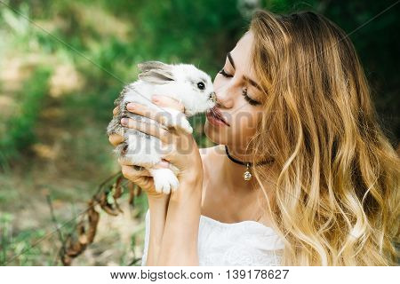 Pretty young woman long-haired kisses cute little rabbit on summer day on natural background
