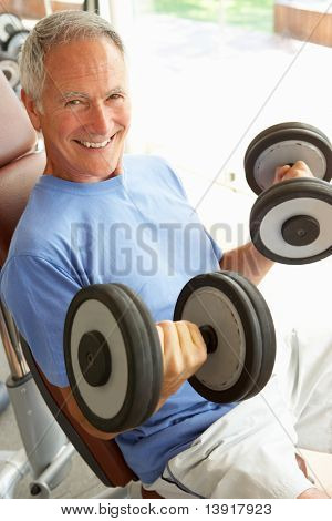 Senior Man Working With Weights In Gym