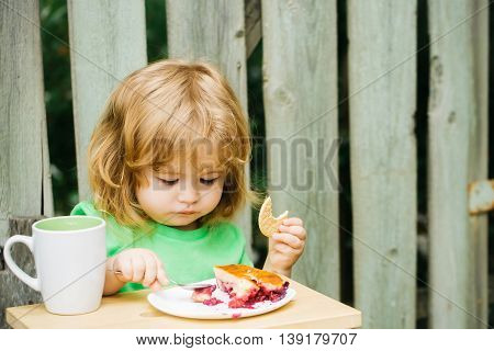Small Boy Eating Pie Near Wooden Fence