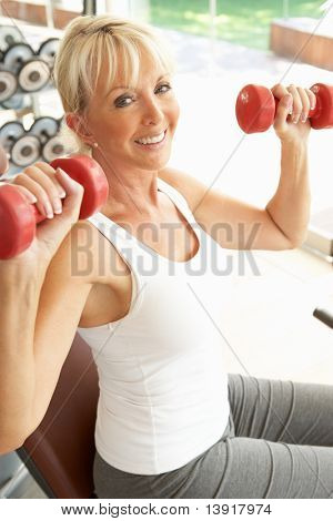Senior Woman Working With Weights In Gym