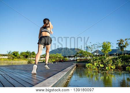 The back view of woman running in a park