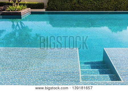 Swimming pool made by mosaic tiles with small stairs inside the clear blue water which not moving. Water surface reflects shadow of sky tree and bush in far background.