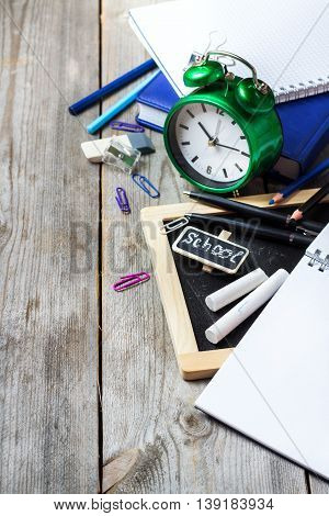 Still life, business, education concept. Assortment of office and school supplies, alarm clock and chalkboard on a rustic wooden table. Selective focus, copy space background