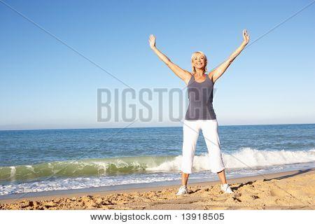 Mulher sênior em roupas de Fitness, alongamento na praia