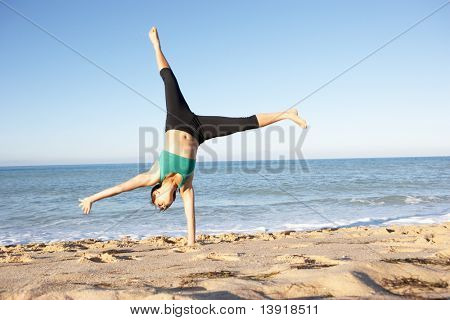 Young Woman In Fitness Clothing Turning Cartwheel On Beach