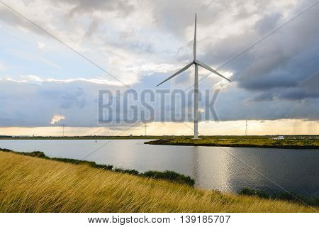 Wind turbine with a total height of 130 meters on the edge of a Dutch canal.