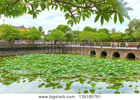 Hue, Vietnam - July 16th, 2011: Lotus Pond in the Forbidden City with architecture bastion in middle as they were in handheld create beauty attracts tourists, it  recognized world cultural heritage