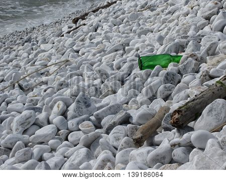 Garbage on the beach . Particular of a green bottle abandoned between the pebbles