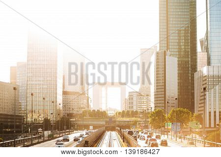 Skyscrapers with glass facade and Grande arch. Modern buildings in Paris business district. Concepts of economics financial future. Copy space. Sunset. Evening traffic.