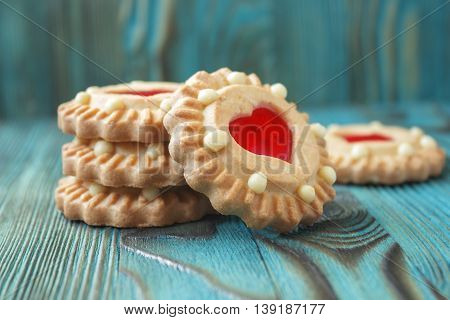 Freshly baked sweet jelly cookies with red filling like a heart on plate on emerald blue wooden background