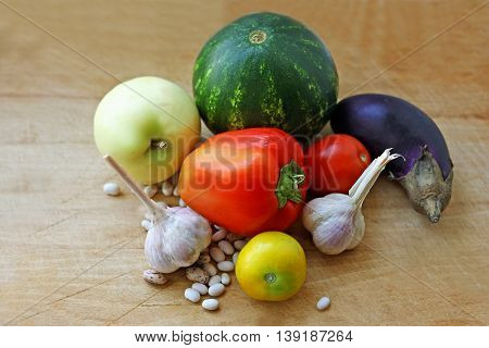 Ripe pumpkin tomatoes watermelon garlic apples pepper eggplant and beans are on old scratched wooden surface.