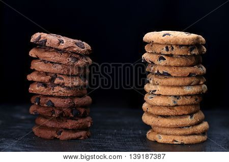 Cookies With Chocolate Chip  On Dark Wooden Table. Two Cookies Towers Isolated On Black Background.