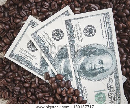Dollars and coffee beans background photo closeup