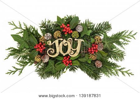 Christmas decoration with gold glitter joy sign, holly and red berries, ivy, snow covered pine cones, cedar cypress and fir leaf sprigs over white background.