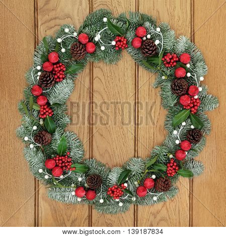 Christmas wreath decoration with red bauble decorations, holly, snow covered blue spruce fir and mistletoe over oak wood front door background.