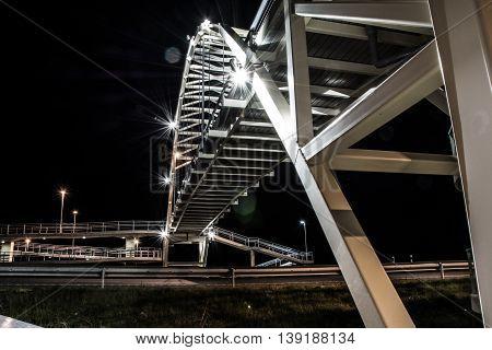 Iron bridge with car lightsin the night. Night city landscape.