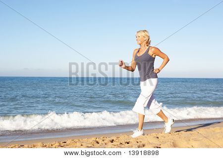 Senior Woman In Fitness Clothing Running Along Beach